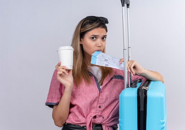 A lovely young woman wearing red shirt and sunglasses looking while holding plane tickets with blue suitcase on a white wall