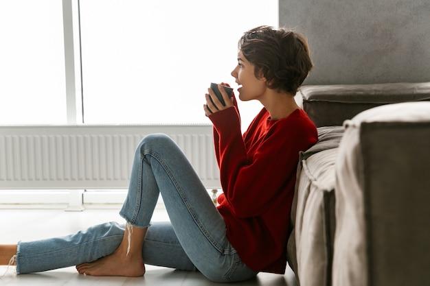 Милая молодая женщина в свитере сидит на полу дома и пьет чай