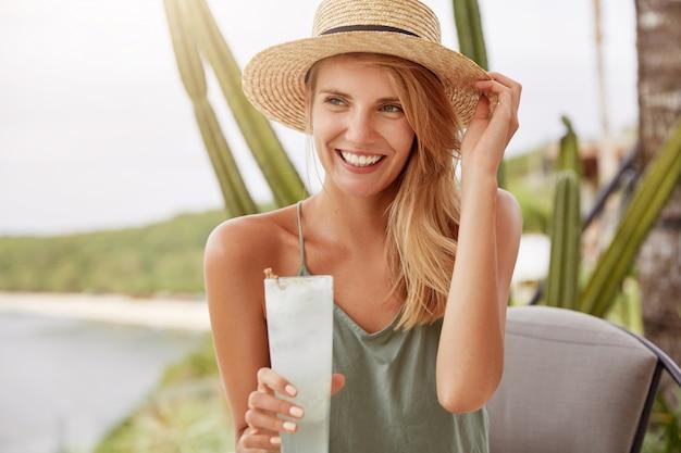素敵な若い女性は麦わら帽子とカジュアルなtシャツを着て、新鮮なカクテルを飲み、遠くに夢のような表情で見えます。エキゾチックな飲み物を持つ女性モデル。カフェテリアで愛らしい女性を再現