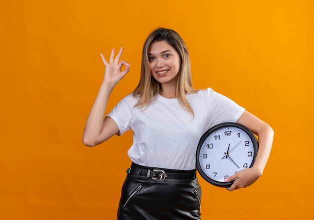 Una bella giovane donna in una maglietta bianca che mostra il segno giusto mentre tiene un orologio da parete su una parete arancione