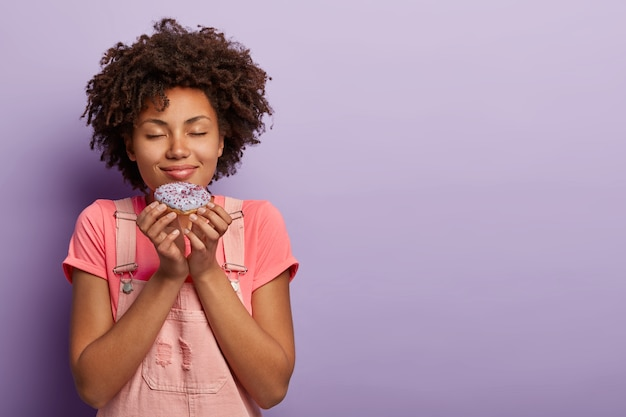 オーバーオールでポーズをとるアフロの素敵な若い女性