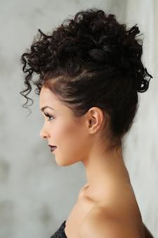 Bella giovane donna con i capelli ricci neri e abito nero lucido
