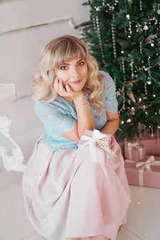 Lovely young woman with elegant style sitting indoor near decorated tree with pink christmas presents