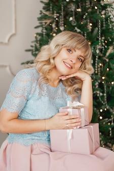 Прекрасная молодая женщина с элегантным стилем сидит в помещении возле украшенного дерева с розовыми рождественскими подарками