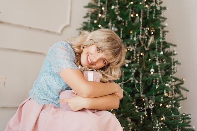 핑크 크리스마스 선물 장식 된 나무 근처에 실내에 앉아 우아한 스타일과 사랑스러운 젊은 여자