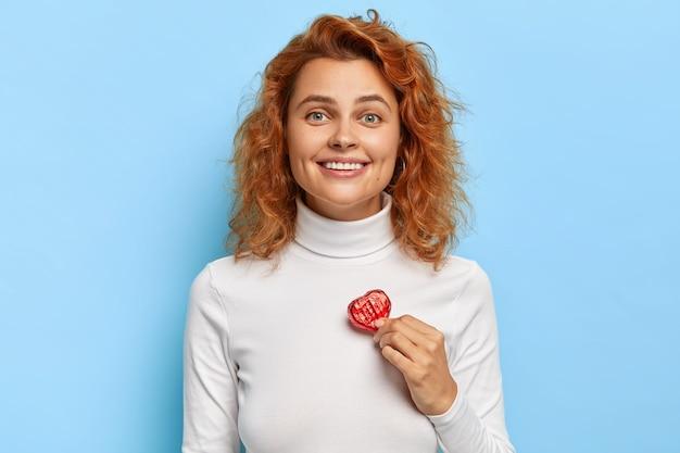 Прекрасная молодая женщина с рыжими волосами держит маленькую конфетку в форме красного сердца