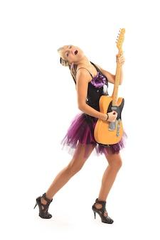 白い背景にポーズをとってギターを持つ素敵な若い女性
