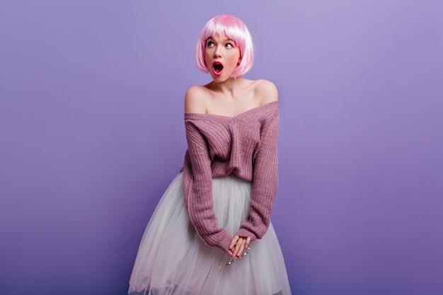 Прекрасная молодая женщина с розовыми блестящими волосами, игриво глядя в сторону. милая девушка носит фиолетовый свитер и белую юбку.