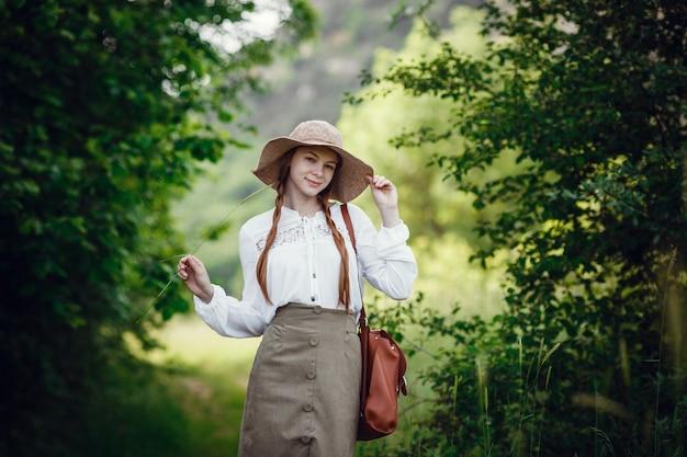 빨간 머리, 모자 및 숲의 가장자리에 배낭과 함께 사랑스러운 젊은 여성. 산책에 아름 다운 redhaired 소녀