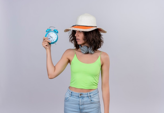 A lovely young woman with short hair in green crop top wearing sun hat looking at a blue alarm clock on a white background