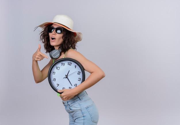 Una bella giovane donna con i capelli corti in top corto verde che indossa occhiali da sole e cappello da sole che indica l'orologio da parete con il dito indice su sfondo bianco
