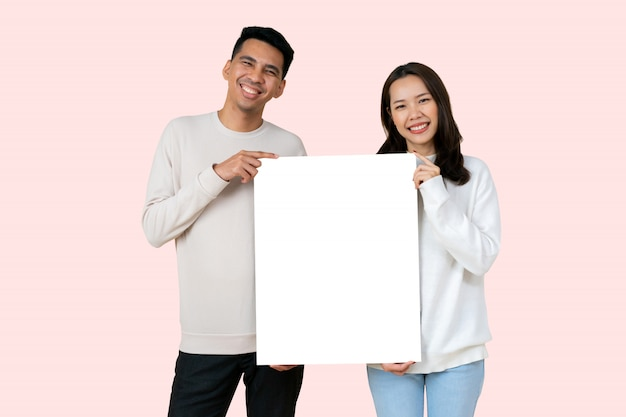 Lover asian people hold white mockup board together isolated on pink color background for valentine day