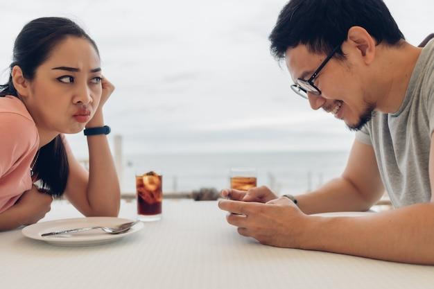 恋人のカップルは、ビーチのレストランで悪いデートをしています。