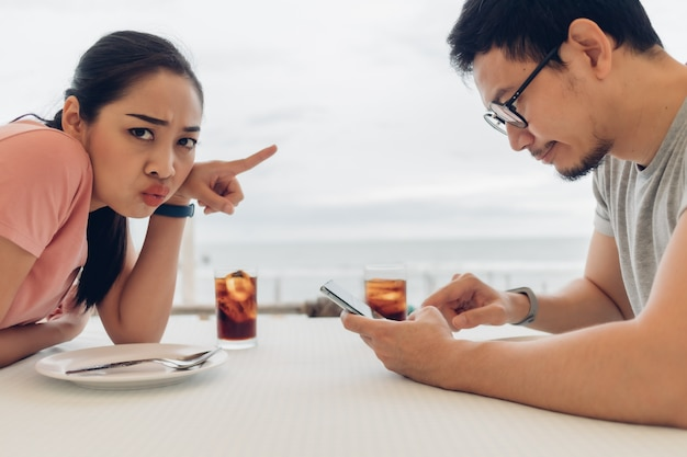 Lover couple is having a bad date at the restaurant on the beach.