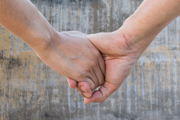 Lover hold hand on aged vintage gray cement wall texture background