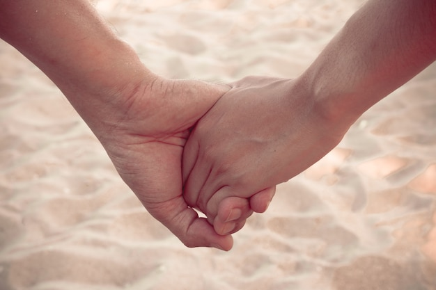 Lover hold hand on the beach with sand wave, vintage style
