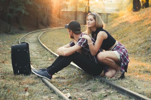 연인들은 철로에서 기차를 기다리고 있습니다 절망적 인 여행자는 가을에 기차 뒤에 지체됩니다