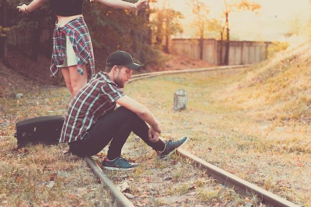 연인들은 철로 위에서 기차를 기다리고 있다 기차 뒤에 뒤처진 절망적인 여행자들