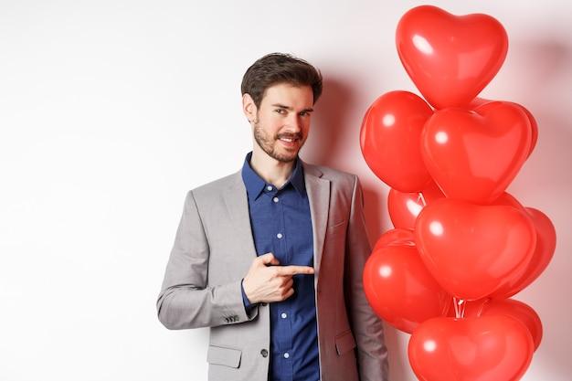 연인의 날. 수염을 가진 매력적인 젊은 남자, 멋진 양복을 입고, 흰색 배경 위에 서 발렌타인 하트 풍선 깜짝 손가락을 가리키는.