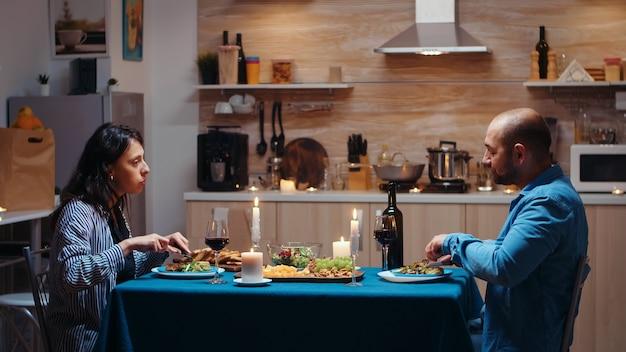 Amanti che cenano insieme, mangiano e bevono vino durante la cena festiva in cucina. coppia felice che parla, seduta a tavola gustando un pasto a casa che trascorre del tempo romantico insieme luci di candela a sorpresa
