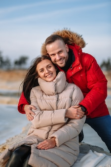 Lovers in down jackets on the dunes of sand pits, around which the ice