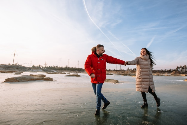 Lovers in down jackets walk on the ice of sand pits