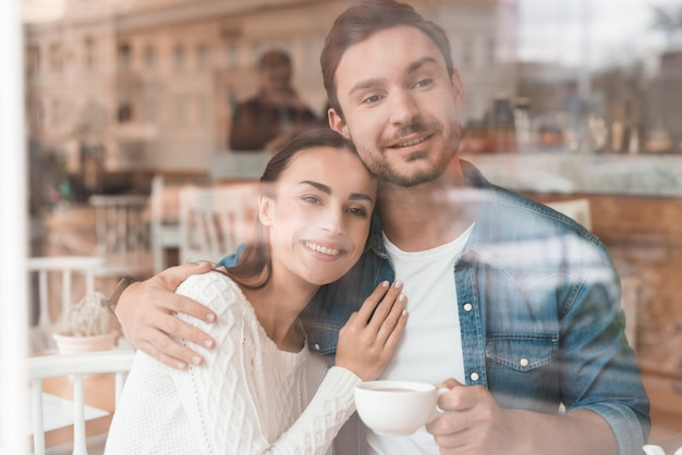 Lovers drink latte in cozy cafe woman gives hug.
