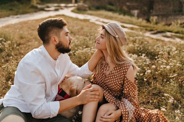연인들은 개 옆 잔디밭에 앉아 서로의 눈을 부드럽게 바라 봅니다. 남자는 여자 친구를 부드럽게 쓰다듬습니다.