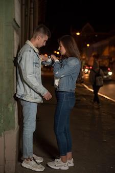 夕方の路地で恋人の男と女。女の子は時間を見て急いで家に帰ります。日付の終わり。夜の街。