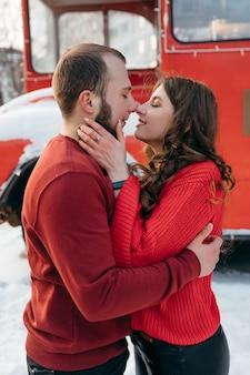 Влюбленные парень и девушка целуются на фоне красного автобуса. фото высокого качества