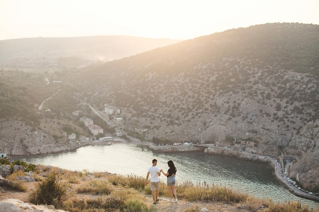 Lovers, guy and girl, on the edge of the cliff against the backdrop of mountains and ocean.