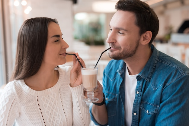 Lovers have cappuccino with straws in cozy cafe.
