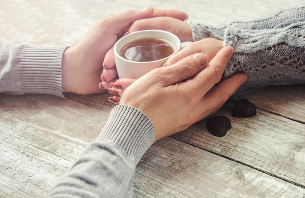Lovers holding together a cup of tea. selective focus.