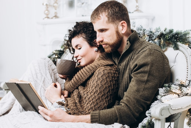 Lovers hugging and reading book in christmas decorated interior