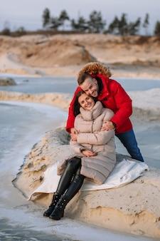 砂場の砂丘にダウンジャケットを着た恋人