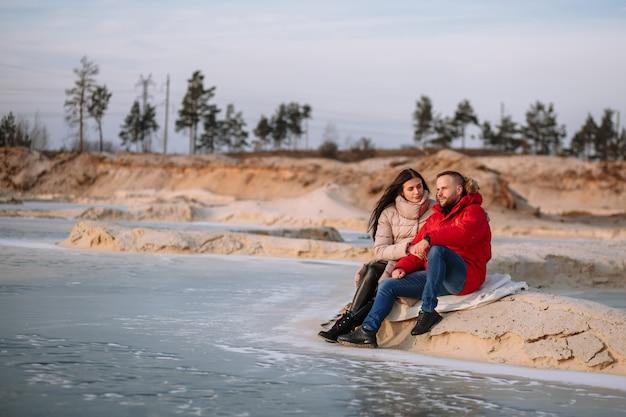 ダウンジャケットの恋人たちは砂場の氷の上を歩く