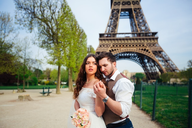 Lovers kissing in paris with the eiffel tower in the wall