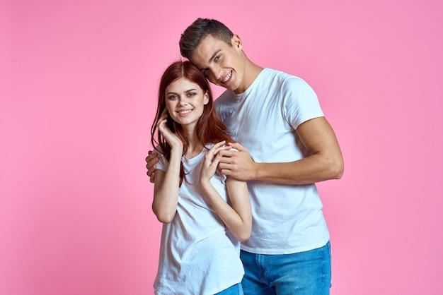 ピンクの背景のトリミングされたビューのジーンズとtシャツの恋人の男性と女性。
