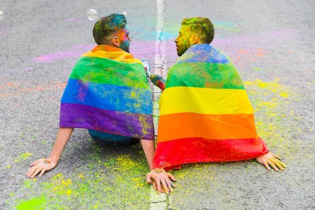 Lovers men sitting on asphalt road