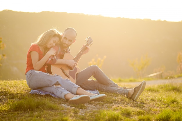 Lovers in nature. young couple in love sitting on the park  while these young guitar playing guitar in sunset time.