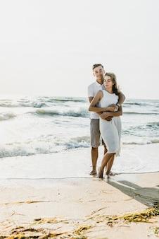 海の近くの愛好家は抱擁し、楽しんでいます。夫と妻は海の近くの日没で抱擁します。休暇中の恋人たち。夏休み。海沿いのロマンチックな散歩
