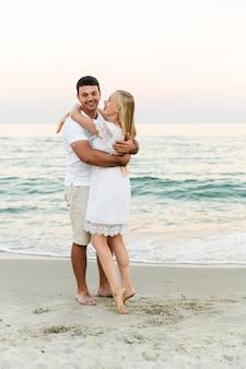 海の近くの愛好家は抱擁し、楽しんでいます。夫と妻は海の近くの日没で抱擁します。