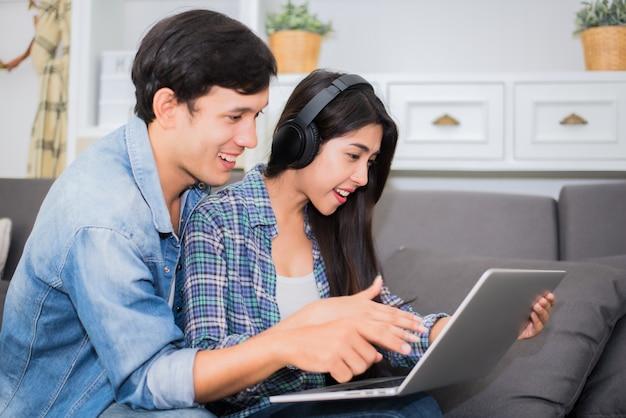 Любители или пара, используя ноутбук и слушать музыку с наушниками в доме