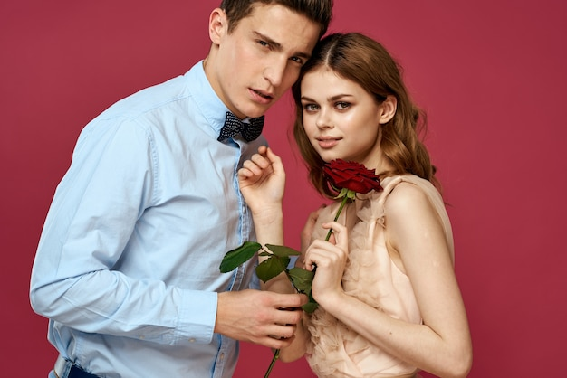Lovers people with rose in hands on pink isolated background hug emotions happiness romance feelings.