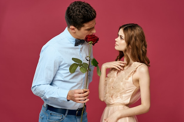 Lovers people with rose in hands on pink isolated background.