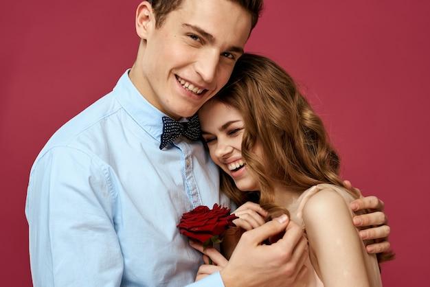 Влюбленные люди с розой в руках на розовом изолированном объятии эмоции счастье романтика чувства