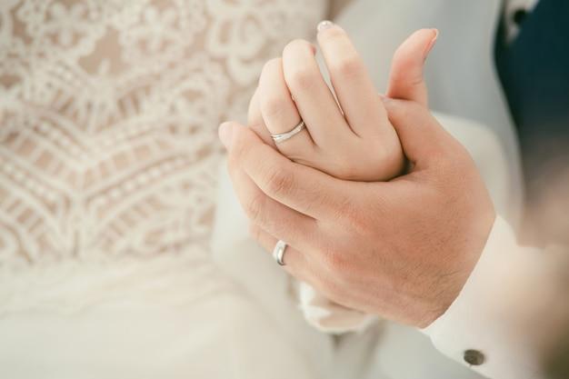 愛好家のリング。手を繋いでいる新郎新婦のカップルは結婚指輪を着用