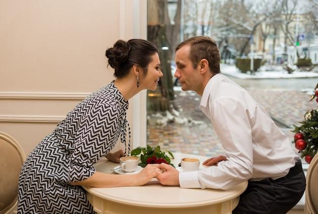 Влюбленные сидят за столиком в кафе с кофейными чашками и розами
