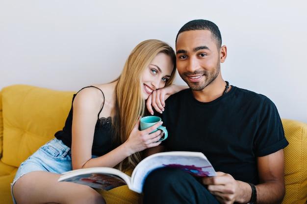 Amanti che sorridono e che guardano in vestiti domestici. coppia che riposa sul divano in camera, legge una rivista, beve il tè, trascorre del tempo insieme, comfort, svago, famiglia, relax.