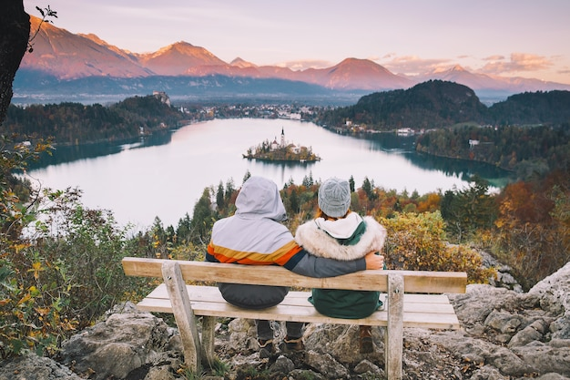 愛好家はスロベニアヨーロッパのブレッド湖の秋または冬を探して恋にヨーロッパのカップルを旅行します